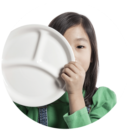 Girl holding plate over face